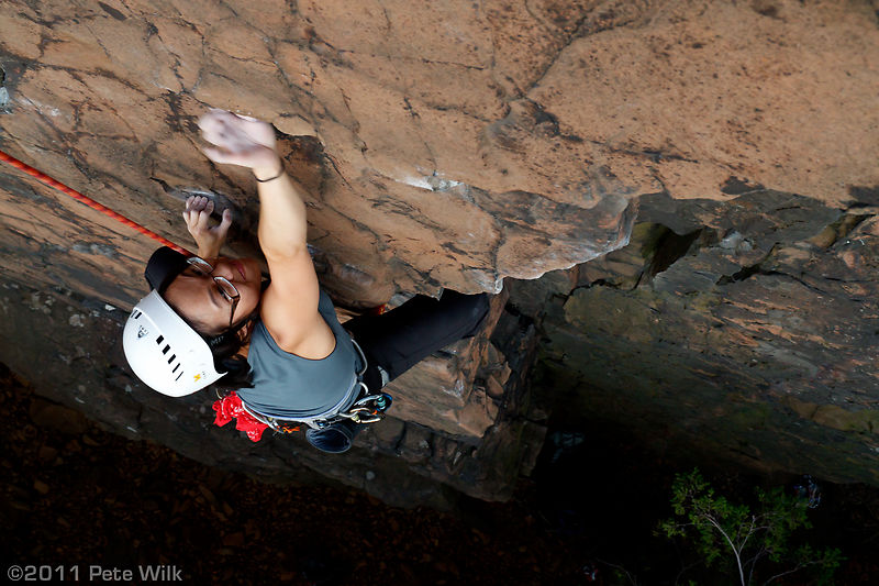 Chrystal strains to reach the small hold under the roof on the first crux of Jaguar (5.10).