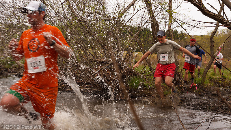 Runners splashing through the final water crossing a few hundred yards from the finish.