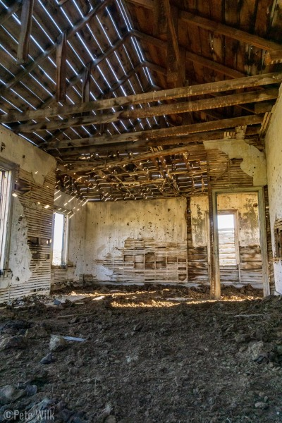 Inside one of the buildings.  Since there are no doors cows have ended up sheltering here and the floor is dried up manure.